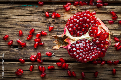 Juicy pomegranate fruit over wooden table