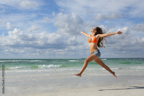Fotografía  Happy woman jumping on the beach on holidays