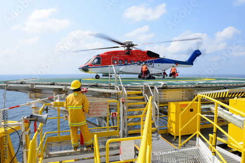 The landing officer are loading baggage of passenger to helicopt