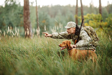 Yang Hunter With Rifle And Dog In Forest