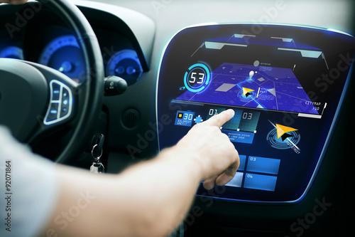 Fotografia  Mężczyzna ręcznie za pomocą systemu nawigacji na desce rozdzielczej samochodu