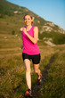beautiful young woman runns cross country on a mountian path at
