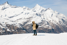 A Man Taking A Photo With Vintage Film Camera On The Snow In The Background Of Snow Mountain.