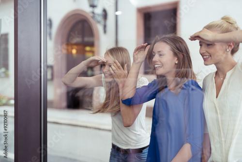 Drei freundinnen schauen durch das schaufenster in ein geschäft Poster