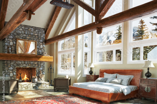 Canvas Print Luxurious open floor cabin interior bedroom design with roaring fireplace and winter scenic background