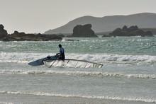 Windsurf En Bretagne. Un Sportif Entre Dans L'eau Pour Pratiquer Son Sport.