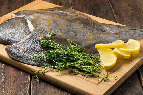 Fototapeta Raw fresh flounder with thyme and lemon on the board