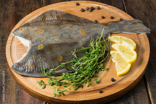 Carta da parati Fresh raw plaice with pepper, thyme and lemon on the board