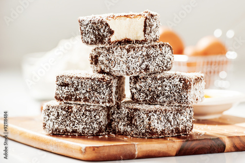 Fotografie, Obraz  Group of Lamingtons on a timber cutting board with food ingredients in the backg