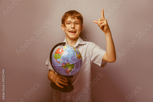 Fotografia  a boy of 10 years of European appearance with glasses holding a