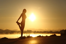 Silhouette Of A Fitness Woman Stretching At Sunrise