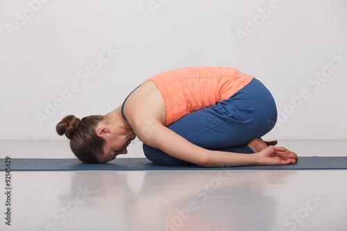 Beautiful sporty fit yogi girl practices yoga asana balasana Wallpaper Mural