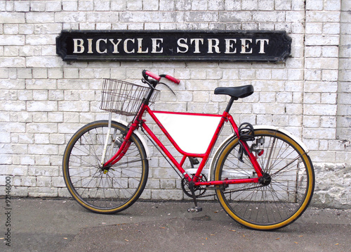 bicycle-street-sign-with-a-bicycle-leaning-against-a-wall-with-an-empty-panel-for-your-logo-or-message