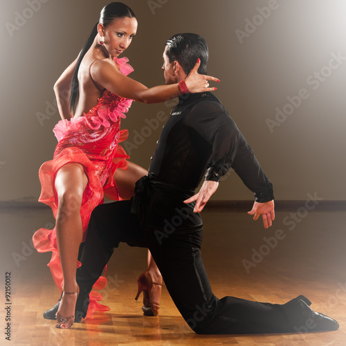 obraz dibond latino dance couple in action - dancing wild samba in a ballroom with light sparcles