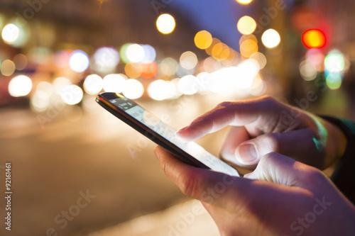 Man using his Mobile Phone in the street, night light bokeh Background Tapéta, Fotótapéta