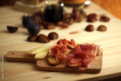 Keuken foto achterwand Voorgerecht autunno con bruschette con fichi e prosciutto castagne e uva