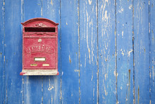 Red Mailbox With Blue Wood Background