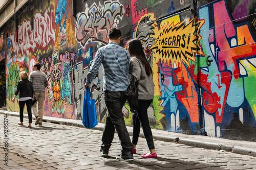 Naklejka premium ludzie chodzą po ścianie graffiti w Melbourne