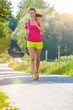 Junge Frau läuft lächelnd Feldweg entlang