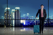 Asian business man carry suitcase with city background