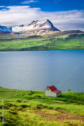 Small cottage in the mountains above the fjord in Iceland