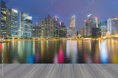Photo  Opening wooden floor, Marina bay business office during twilight with water refl