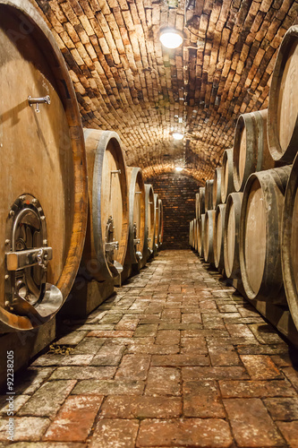 Canvas Print Oak barrels in a underground wine cellar