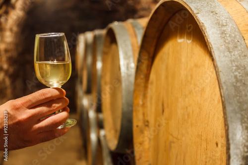 Fototapeta  Ruka držící sklenku bílého vína, ve sklepě
