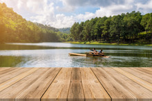 Wooden Board Empty Table In Front Of Blurred Background. Perspective Brown Wood Over Blur Lake In Forest - Can Be Used For Display Or Montage Your Products. Spring Season. Vintage Filtered Image.