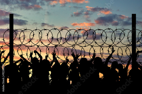 Obraz na płótnie Silhouette of refugees and barbed wire