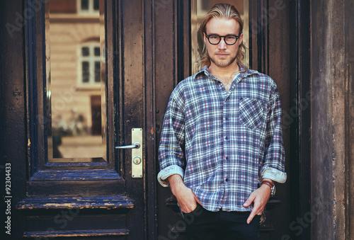 Fotografie, Obraz  Portrait of a smart serious young man standing against building