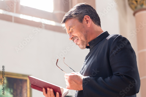 Obraz na plátně Catholic priest reading bible in church