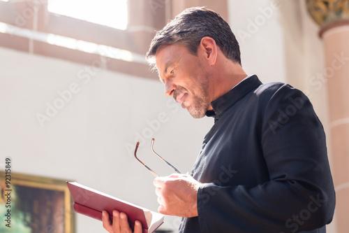 Cuadros en Lienzo Sacerdote católico Biblia de la lectura en la iglesia