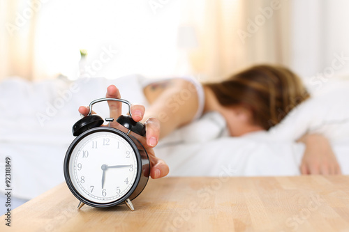 Fototapeta Sleepy young woman trying kill alarm clock