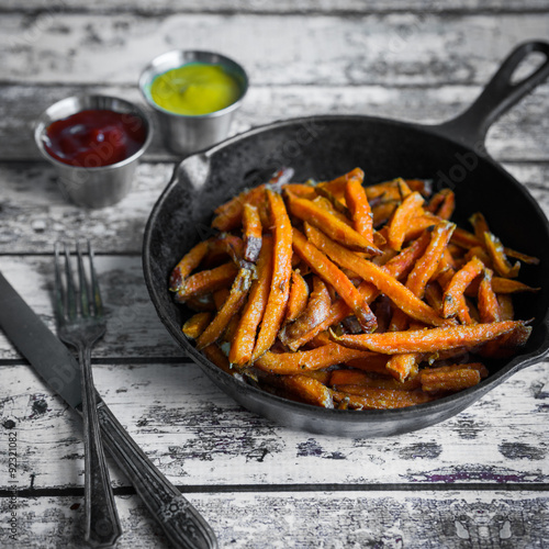 Sweet potato fries in cast iron skillet on wooden background Poster
