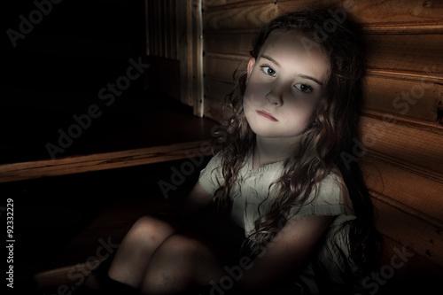Photo Depressed girl sitting in a dark hallway in home