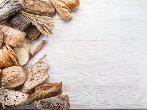 Tuinposter Brood The bread and a wheat on the wooden desk.