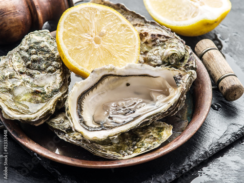 Raw oysters on the graphite board. Canvas Print