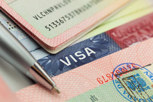 Different Visas And Stamps In A Passport - Travel Background