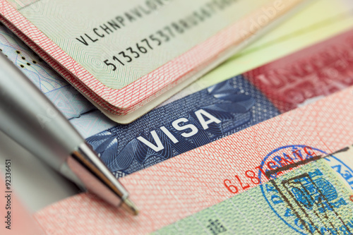 Different visas and stamps in a passport - travel background Fototapet
