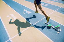 Athlete In Gold Shoes Sprinting From The Starting Blocks Over The Starting Line Of A Race On A Blue And Tan Running Track
