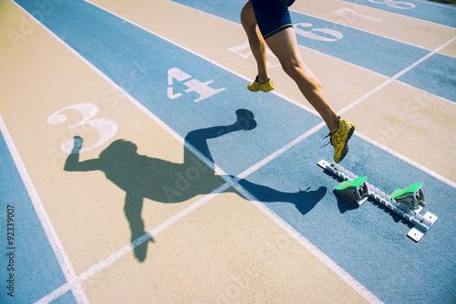 Fotografía  Atleta en zapatos de oro corriendo desde la parrilla de salida sobre la línea de