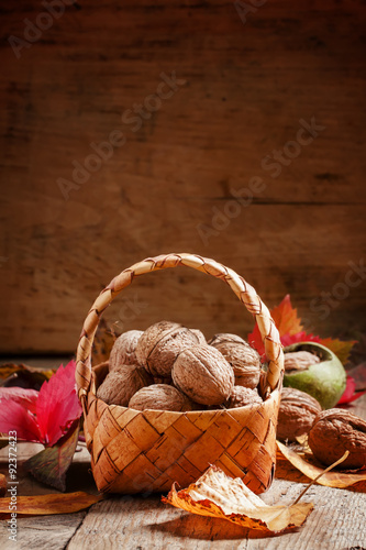 Stickers pour portes Pique-nique Autumn harvest of walnuts in a wicker basket on an old wooden ba