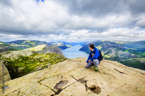Plakat  A young man on the mountain admiring view over Lysefjord. Norway.