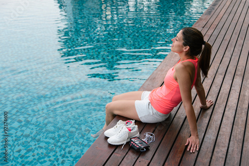 Sporty woman relaxing at poolside after fitness workout. Sportive female with feet into pool water. Athlete resting.