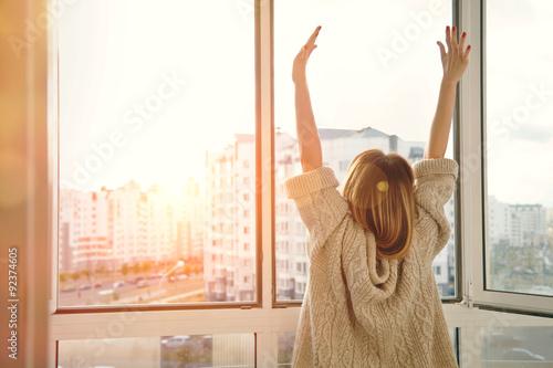 Obraz Woman near window raising hands facing the sunrise at morning - fototapety do salonu