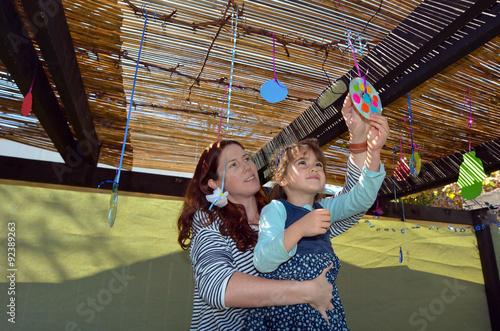 Obraz na plátne Jewish woman and child decorating their family Sukkah