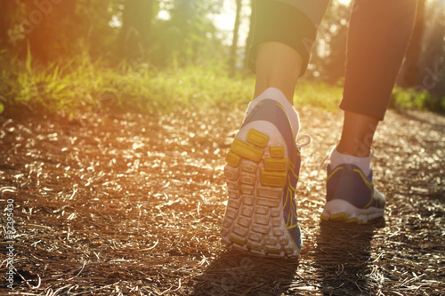 Fotografie, Obraz  Athlete runner feet running in nature, closeup on shoe