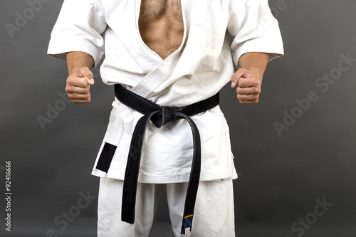 Foto op Canvas Vechtsport Young man in white kimono and black belt training martial art