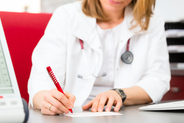 Doctor writing medical certificate in practice